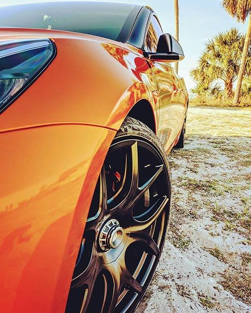 Orange wrapped customized Tesla Model 3 wheel closeup.