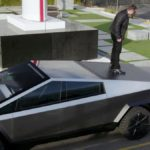 Elon Musk standing on the Tesla Cybertruck, Jay Leno and Franz von Holzhausen looing up to him.