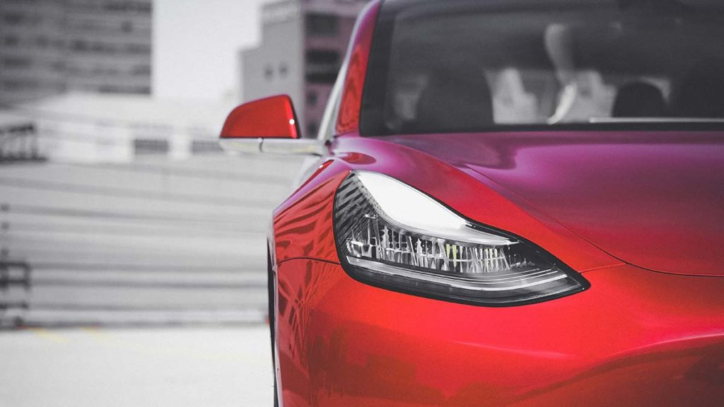 Red Tesla Model 3 - Headlight and half front fascia closeup.