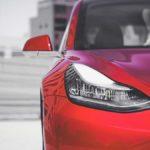 Red Tesla Model 3 - Headlight and half front fascia closeup.
