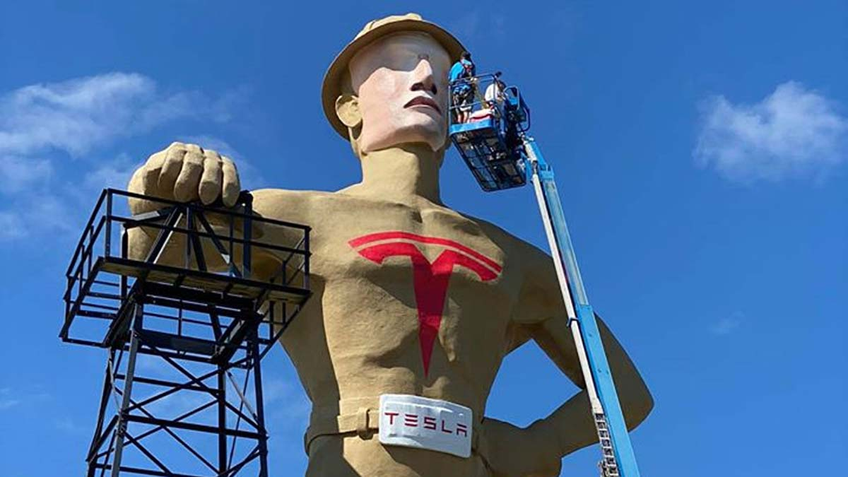 Golden Driller statue painted with Tesla logo and face transformed to Elon Musk.