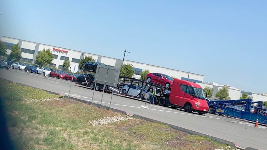 Red Tesla Semi loaded with Tesla Model Y and Model 3 cars leaving for deliveries.