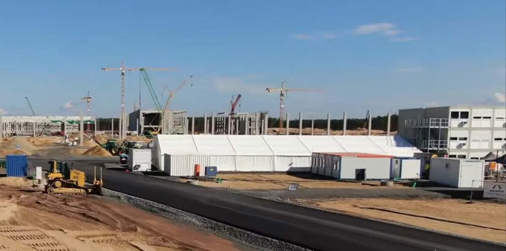 Tent built at the Tesla Gigafactory Berlin construction site, newly build asphalt road also visible.