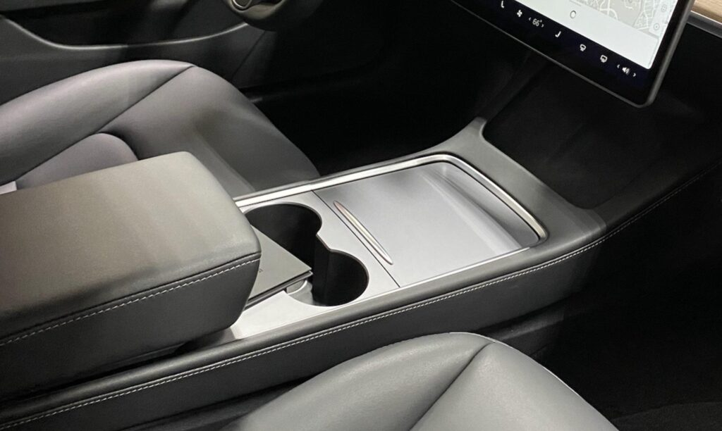 The updated Tesla Model 3 center console with vegan leather and stiching and a new matte black texture for the lid.