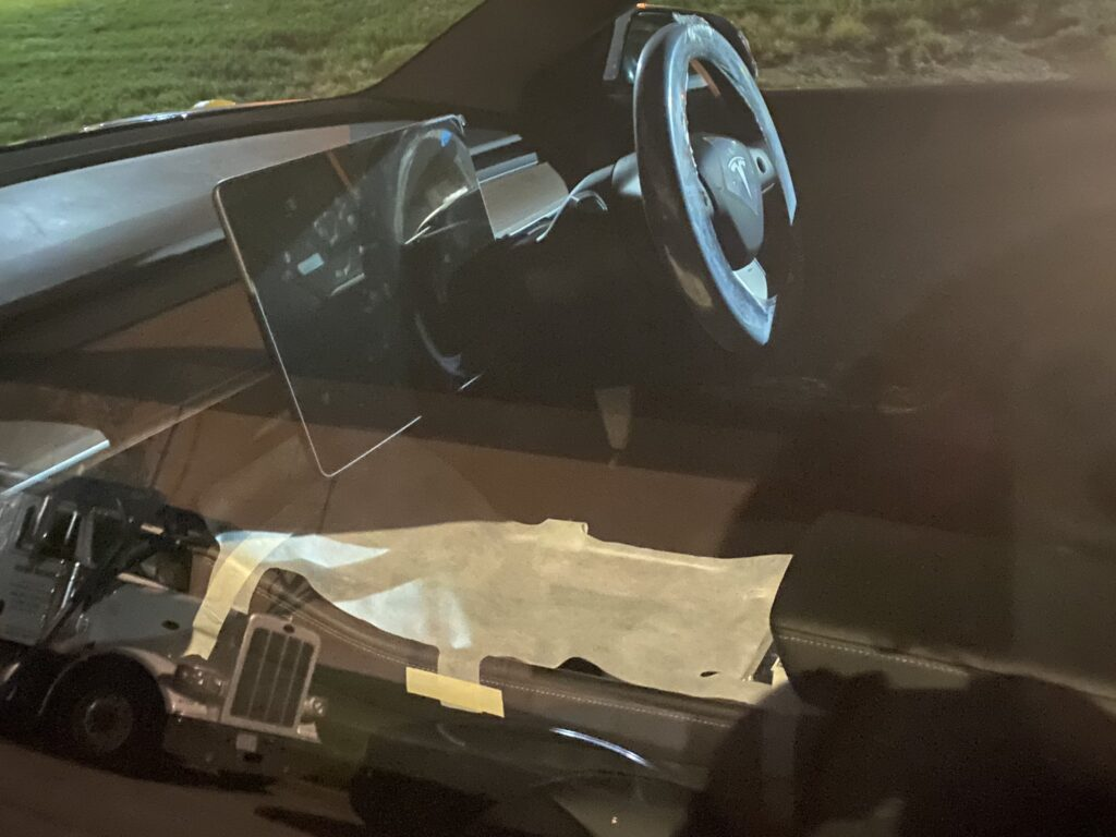 Spy shot of the new Tesla Model 3 interior showing the center touchscreen and the center console.