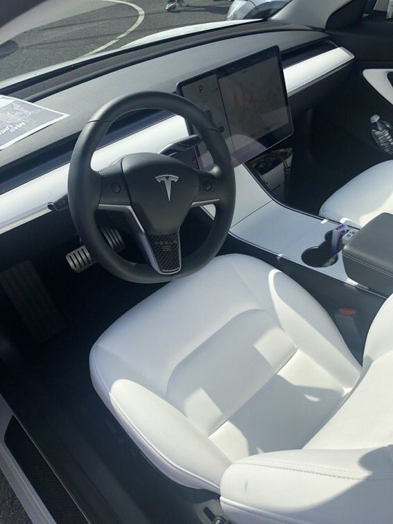 Old Tesla Model 3 center console with piano black finish.