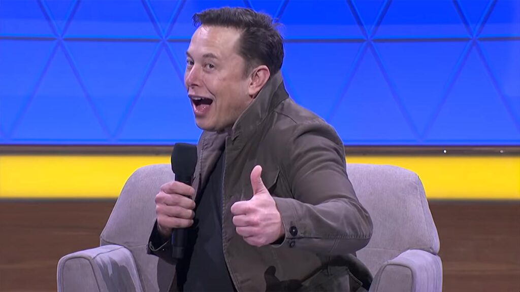 Elon Musk showing a thumbs up expression.