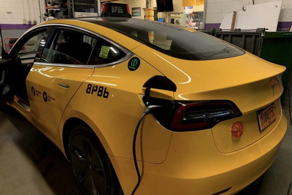 Tesla Model 3 yellow cab charging.