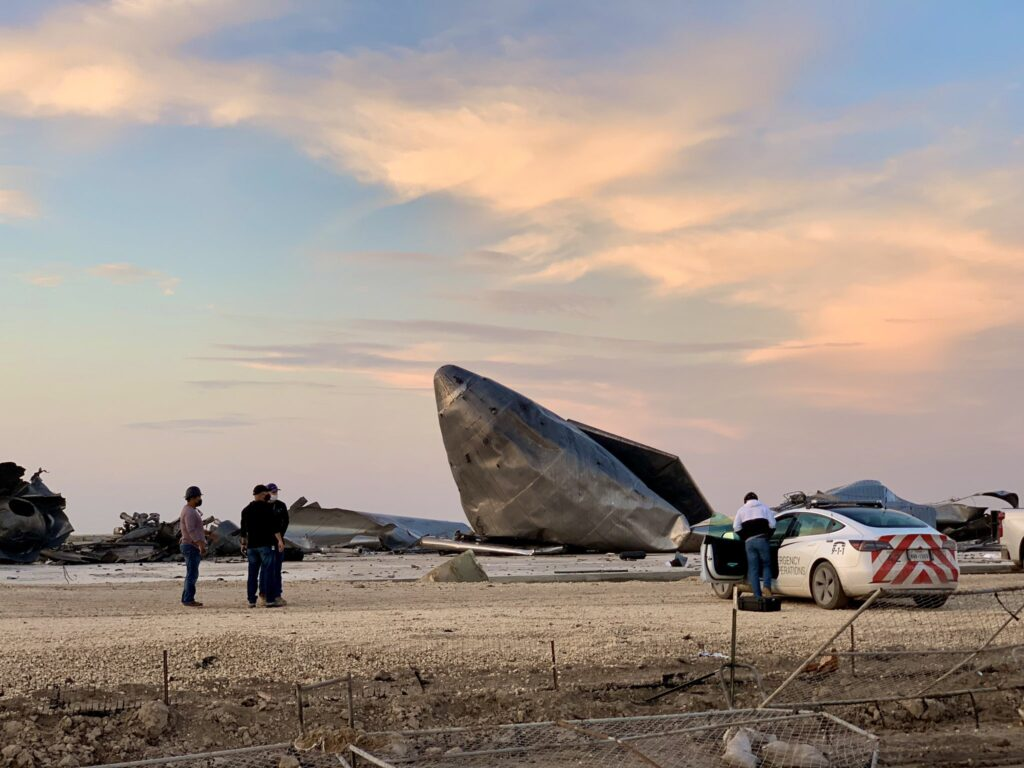 Starship SN8 nose cone after the landing explosion. SpaceX Emergency Operations Tesla Model 3 at the site.