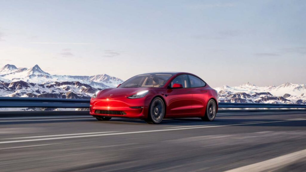 New Tesla Model 3 in red, accelerating on the highway.