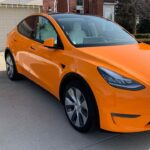 Orange wrapped Tesla Model Y electric SUV (cost, service provider, photo gallery).