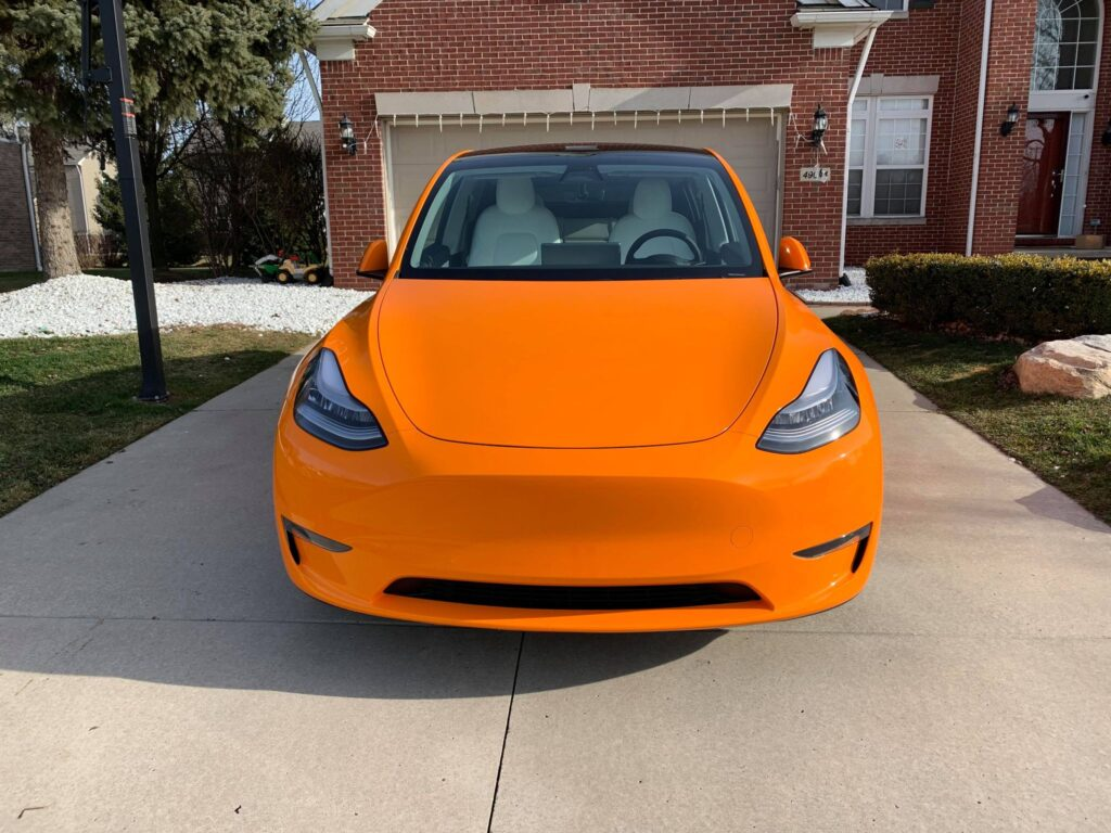 Orange wrapped Tesla Model Y front fascia.