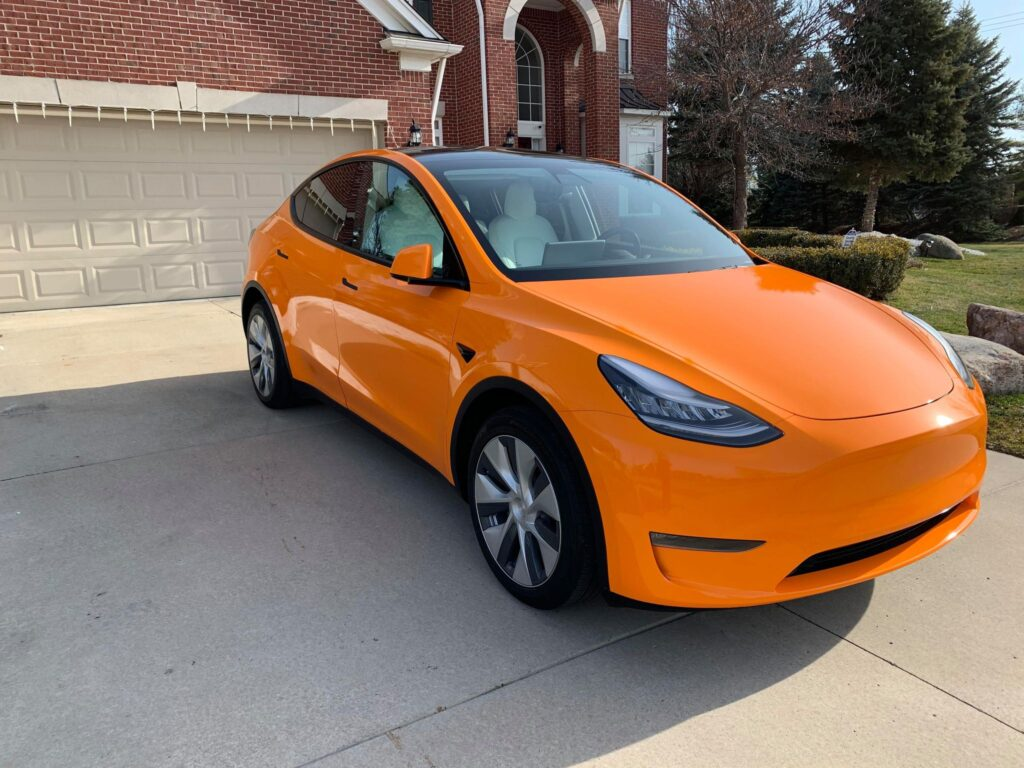 Orange wrapped Tesla Model Y (front side view).