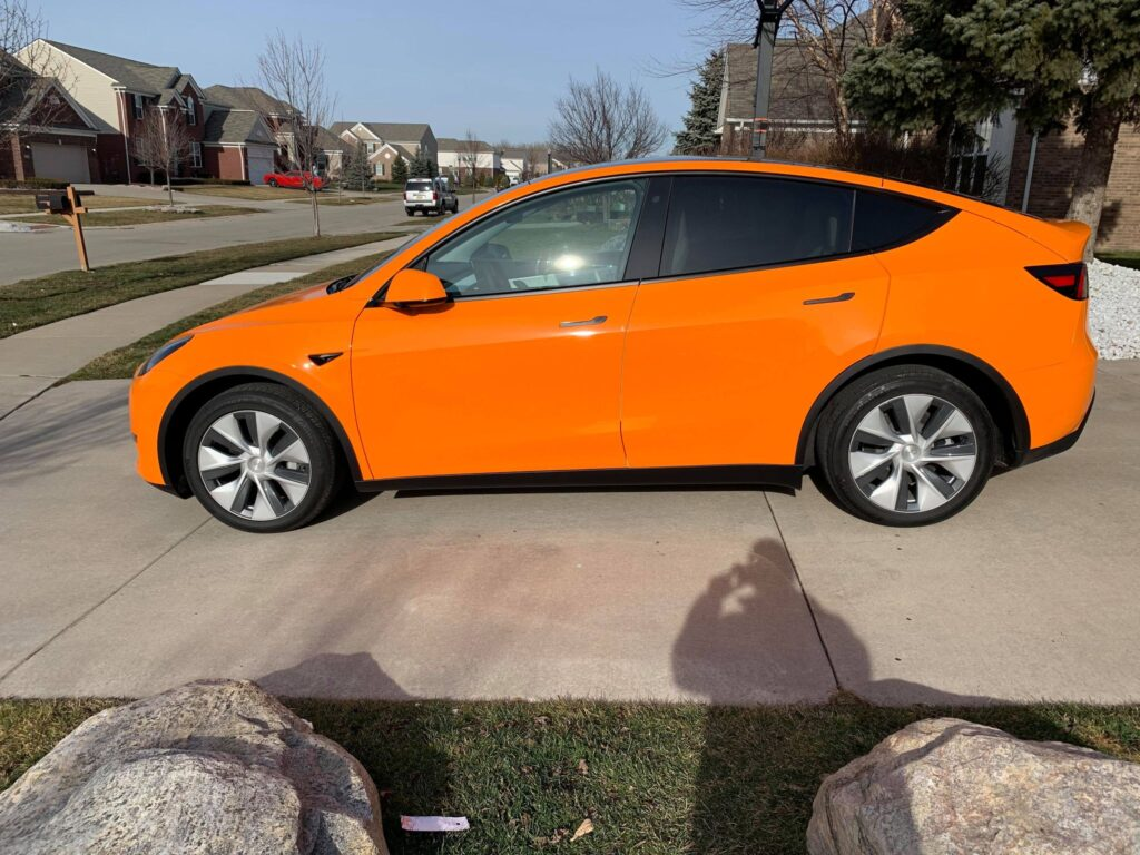 Orange wrapped Tesla Model Y full side profile view.