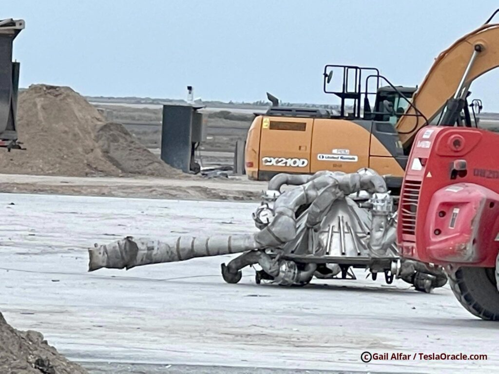 Starship SN10 wreckage being dragged to the SpaceX building.