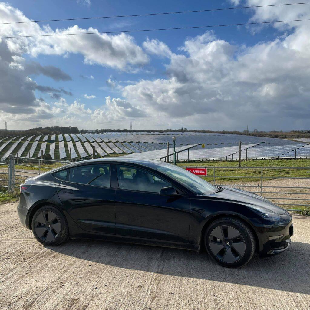 Mathew's black MIC Tesla Model 3 Long Range, parked in front of solar park in the UK.