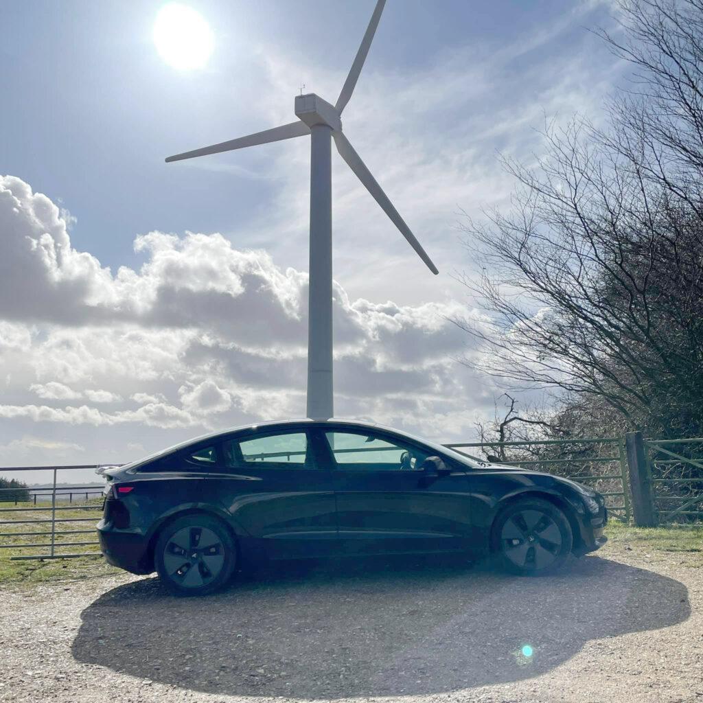 Tesla Model 3 Standard Range Plus parked in front of a wind turbine in the UK.