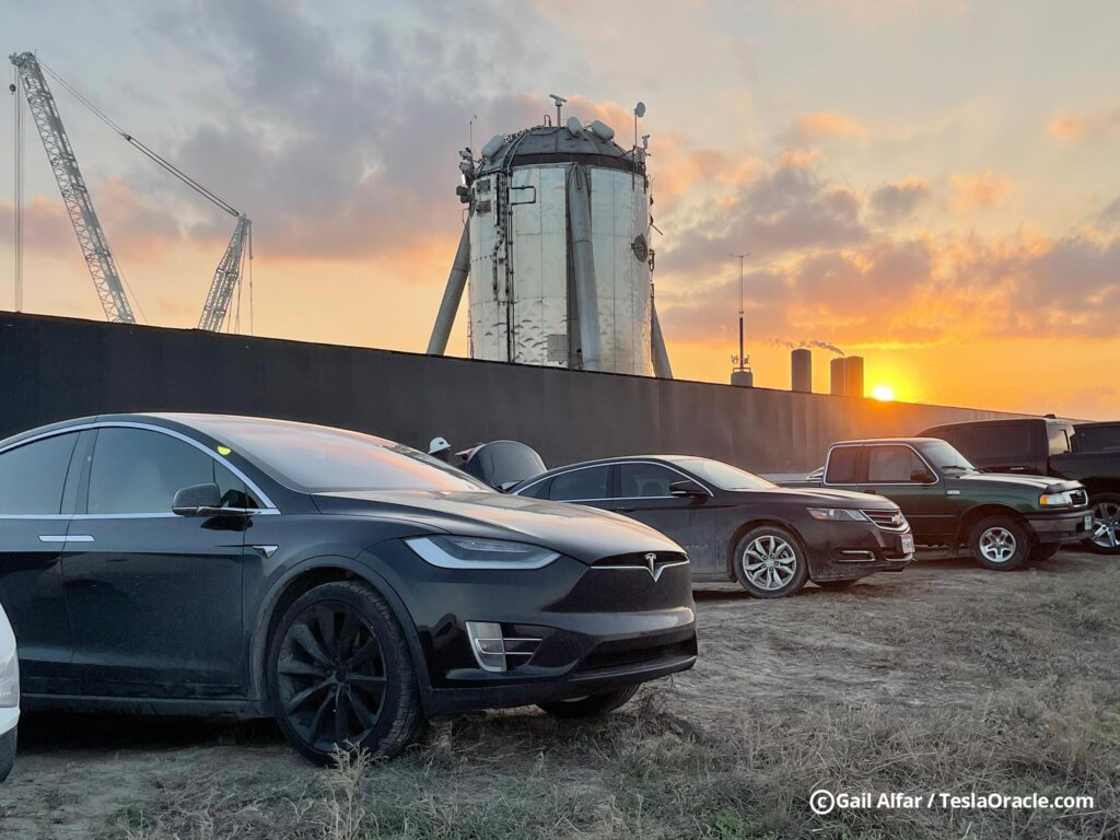 A Tesla Model X and other vehicles parked at SpaceX, tank farm visible in the background.