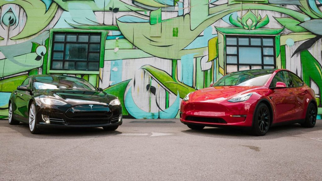 Tesla Model S and Model 3 parked in front of a wall covered in graffiti art.