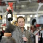 Elon Musk holding champagne in hand as celebration.