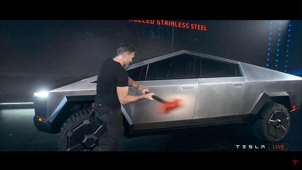 Franz von Holzhausen hitting the Tesla Cybertruck with a sledgehammer at the unveil (door handles visible).