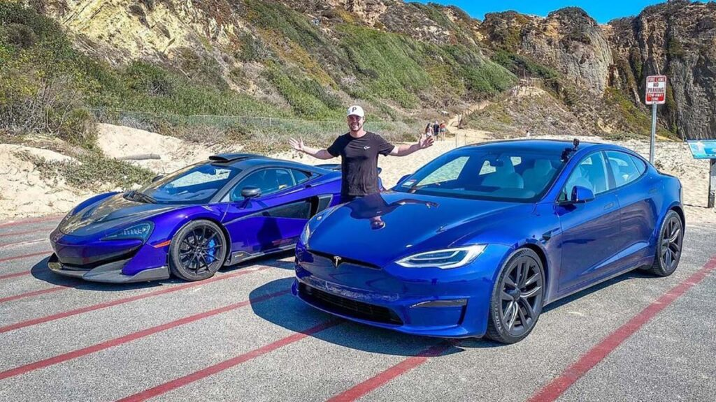 Tesla Model S Plaid and McLaren 600LT both in blue color parked side-by-side for in anticipation of a race.