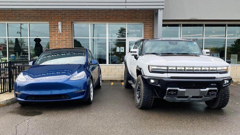 Tesla Model Y (left) and a Hummer EV production-ready prototype (right) parked side-by-side outside Starbucks.